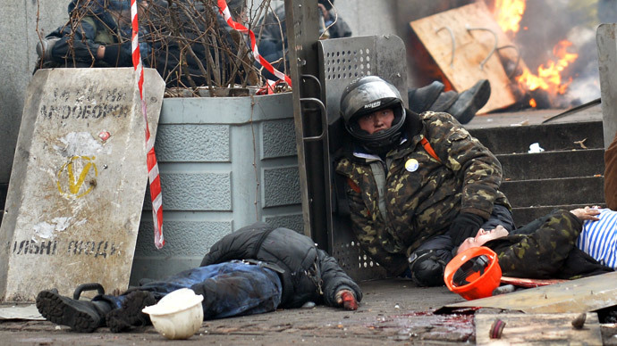 An anti-government protester sit near the bodies of two demonstrators killed by a sniper during clashes with the police in the center of Kiev on February 20, 2014.(AFP Photo / Sergei Supinsky)